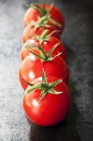 rad med fack tomater på skiffer foto
