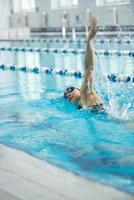 ung flicka i skyddsglasögon som simmar främre krypslagstil foto