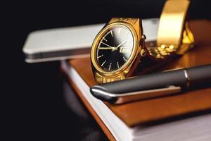 herrtillbehör, gyllene klocka, penna och mobiltelefon på foto