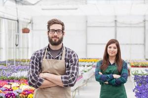 glada män och kvinnlig blomsterhandlare som arbetar inomhus foto