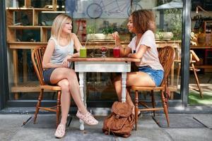 kvinnliga vänner som möts på utomhuscaféet foto