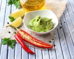 färsk guacamole i skål på träbord foto