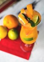 uppfriskande saft med apelsiner och mynta på träbord foto