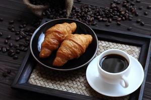 svart kaffe och croissant. foto