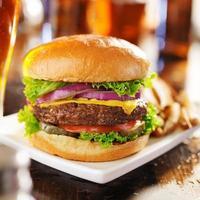 cheeseburger med öl och pommes frites på nära håll foto