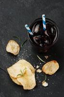 potatischips och glas cola på bordet foto