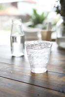 vatten i glas i träbakgrund foto