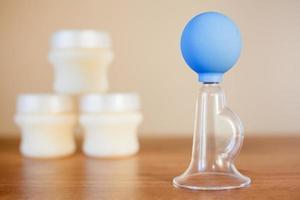 manuell bröstpump och mjölk i bakgrunden foto