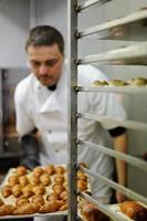 porträtt av baker holdng croissanter bricka foto