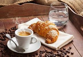 espresso med croissant och ett glas vatten. foto