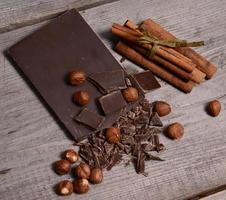 bitar av mörk choklad på en träbakgrund foto