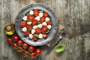 närbild av en mozzarella tomatsallad med basilika foto