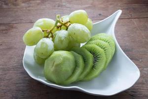grön druva och kiwifrukt på vit maträtt foto
