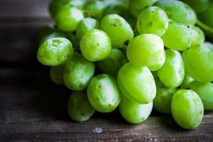 vinstockar av gröna druvor på rustik träbakgrund