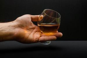 konjakglas i mänsklig hand foto