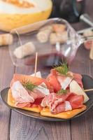 skivor av härdad skinka med melon och rött vin foto