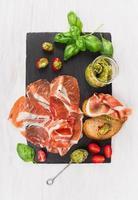 prosciutto skinka med bröd, basilikapesto och tomater på skiffer foto
