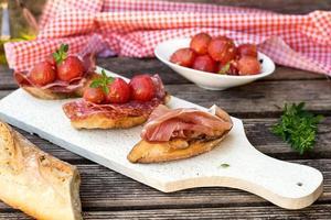 torkad prosciutto på italiensk skinka på brödskål foto