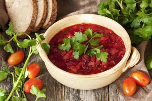 röd soppa borscht i keramisk skål foto