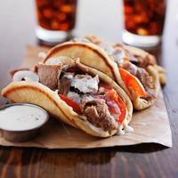 grekiska gyros med tzatzikisås och pommes frites foto