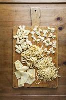 olika typer av färsk pasta på träbakgrunden. spaghet