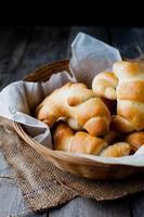 smör rullar bröd i rottingkorgen mot mörk rustik bakgrund foto
