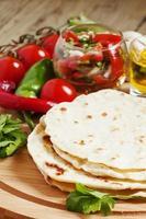hemlagad tortilla på brädet med grönsaker foto