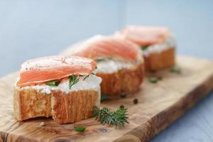 små smörgåsar med mjuk ost och lax på träbord foto