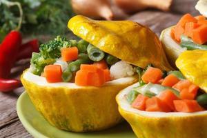 rund gul squash fylld med horisontella grönsaker foto