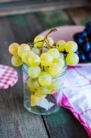 kvist av gröna druvor i ett glas foto