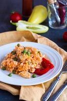 risotto med kyckling, ärtor och tomater, italiensk mat foto