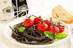 pasta med bläckfiskbläck med grillad tomat foto