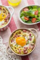 bakad pastaspagetti carbonara med äggula, ost och bacon foto
