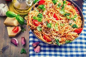 spaghetti bolognese med körsbärstomat och basilika. foto