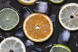skivade citrusfrukter citron, lime, apelsin, grapefrukt med is ov