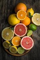 färska citrusfrukter på rustik träbakgrund, ovanifrån foto