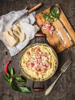 pasta carbonara i vintagen panna med parmesanost, kryddor foto