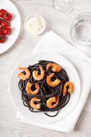 svart italiensk pasta med räkor mat på ljus bakgrund foto