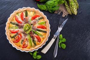 grön asparagisyrta med ägg och tomat foto