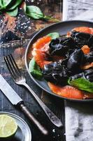 svart ravioli med saltad lax foto