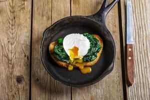 bruschetta med spenat och pocherat ägg foto