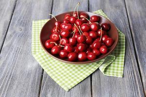 söta körsbär på plattan på träbakgrund foto
