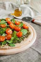 pizza med pesto, spenat och körsbärstomater foto