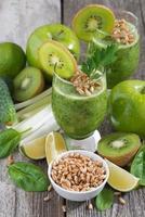 frisk grön smoothie med groddar på ett träbord, vertikal foto