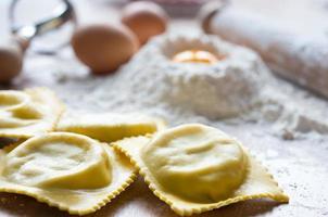 närbild av färska handgjorda ravioli med mjöl och ägg foto