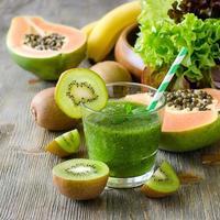 grön tropisk smoothie med kiwi, papaya och salladsblad foto