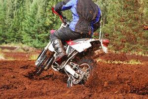 terrängmotorcykel som svänger i smuts foto