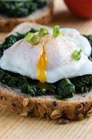 spenat och pocherat ägg på brunt bröd foto
