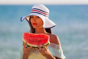 brunett kvinna vattenmelon havet foto
