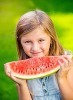 söt liten flicka som äter vattenmelon foto